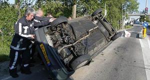 Hulpverleners proberen een gelanceerde auto weer op zijn wielen te zetten.